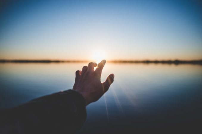Hand pointing to the sun
